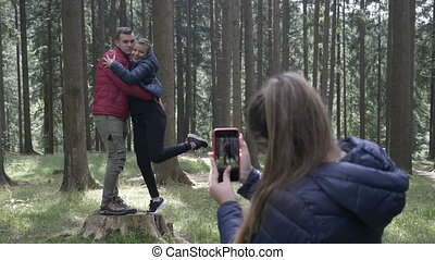 Teenage woman taking photos with her smartphone camera to a young couple hiking in the woods
