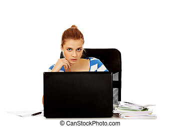 Teenage woman with laptop sitting behind the desk