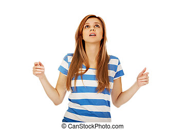 Teenage woman with outstretched arms looking up