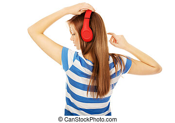 Teenage woman with red headphones