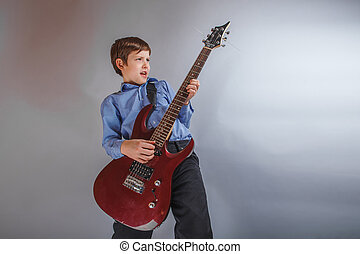 teenager a boy Dark Brown European appearance playing guitar...