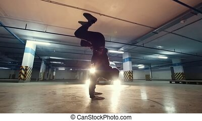 Teenager acrobat at underground parking have workout -...