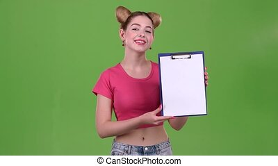 Teenager advertises a tablet for paper. Green screen