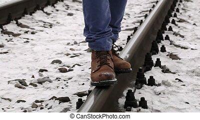 Teenager balancing on rails