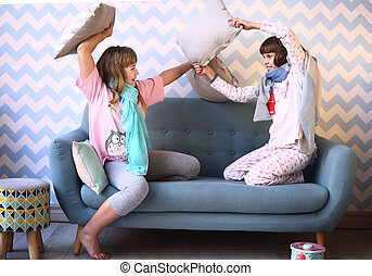 teenager blond sister in pajamas on the sofa