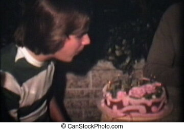 A teenage boy blows out the candles on his unusually pink birthday cake. (Scan from archival 8mm film)