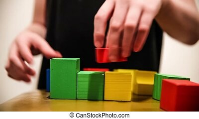 teenager boy builds a tower  of bricks blocks play a major hand video hd 1920x1080
