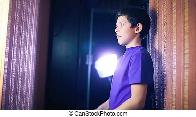 teenager boy child reading a book, yes gesture standing against the wall in the apartment page flipping