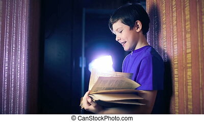 teenager boy child reads a book, standing against the wall in apartment page flipping