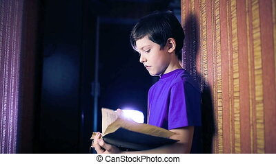 teenager boy child reads a book, standing against the wall in the apartment page flipping