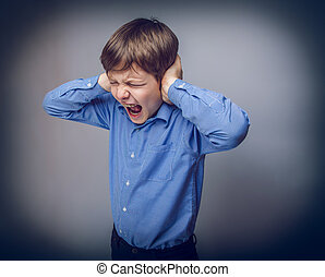 teenager boy closed ears with his hands gray background - ...