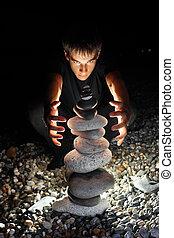 teenager boy conjuring near pyramid from pebble on stony seacoast at night