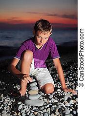 teenager boy creates pyramid from pebble on stony seacoast at night
