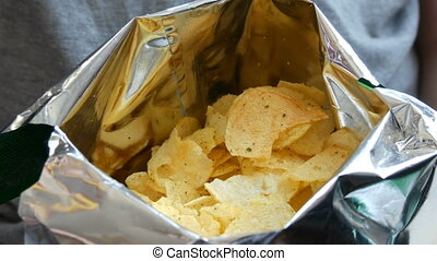Teenager boy eats potato chips from a package. Unhealthy...