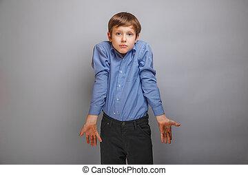 teenager boy in a shirt shrugs