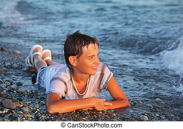teenager boy in wet clothes lying on stones on seacoast