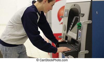 Teenager boy insert credit card in cash machine