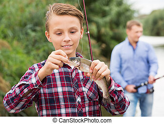 Teenager boy looking at fish on hook - Glad teenager boy ...