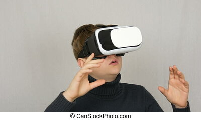 Teenager boy looks into white virtual reality glasses or VR...