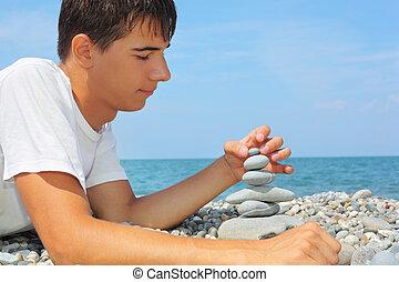 teenager boy lying on stony seacoast, creates pyramid from ...