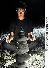 teenager boy meditating near pyramid from pebble on stony seacoast at night