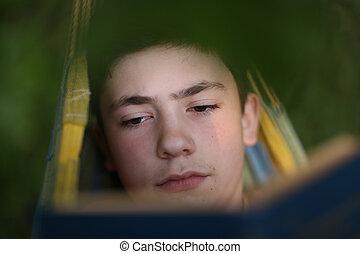 teenager boy reading in hammock