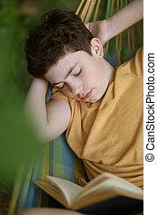 teenager boy sleeping while reading in hammock