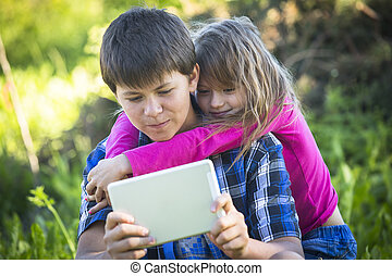 Teenager boy with tablet and his younger sister, outdoors.