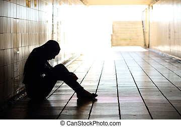 Teenager depressed sitting inside a dirty tunnel - Backlight...