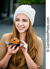 Teenager eating  muffin