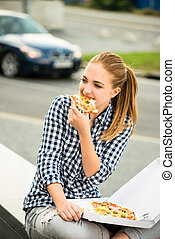 Teenager eating pizza in street