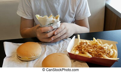 Teenager eats a big chicken roll in a fast food cafe. On the table are large cheeseburgers and French fries.