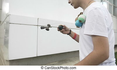 Teenager exercising talent by catching kendama ball on spike...