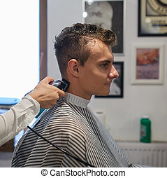 Teenager getting a haircut - Teenager boy in a barber shop...