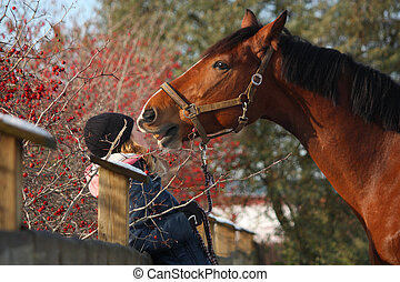 Teenager girl and bay horse hugging each other