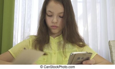 Teenager girl does homework with smartphone stock footage video