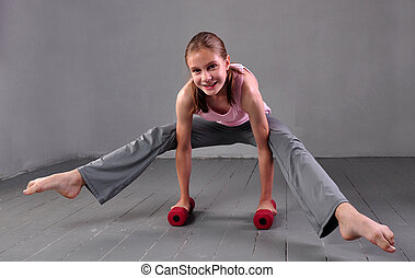 Teenager girl doing exercises with dumbbells to develop with dumbbells muscles on grey background. Full length portrait of teen child exercising with weights.