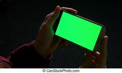 Teenager girl holding smart phone in hands indoor in the dark