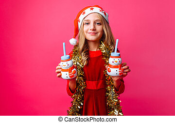 teenager girl in Santa hat and tinsel on the neck, holds 2 bottles of juice Christmas in the shape of a snowman on a red background.