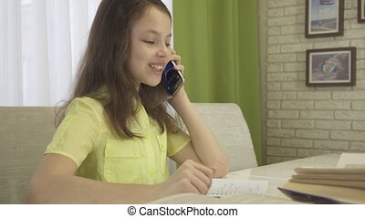 Teenager girl is distracted by telephone conversation while doing her homework stock footage video