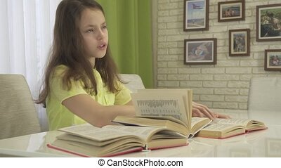 Teenager girl is tired of doing homework, took off the books and got carried away by smartphone stock footage video