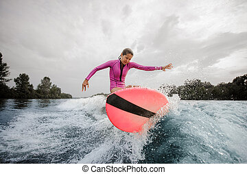Teenager girl jumping on the orange wakeboard