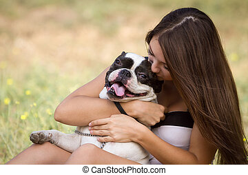 Teenager girl kissing her puppy