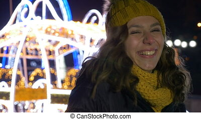 Teenager girl laughing and looking for her boyfriend in Christmas market when he surprises her with a kiss