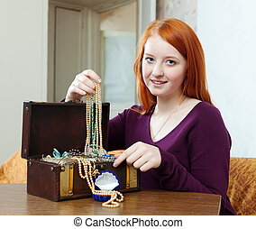 teenager girl looks jewelry in treasure chest