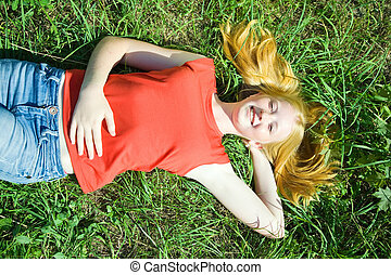 teenager girl lying in grass - Carroty teenager girl lying...