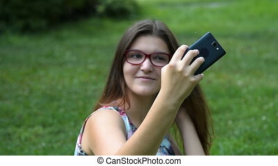 Teenager girl making mobile selfie in the park