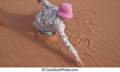 Teenager girl paints on the sand in Rub al Khali desert stock footage video
