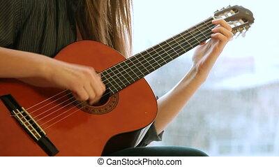 Teen Girl Playing Guitar At Home. Close-Up