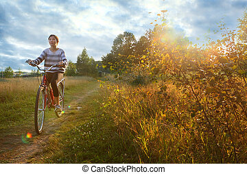 teenager girl ride bicycle on the country field